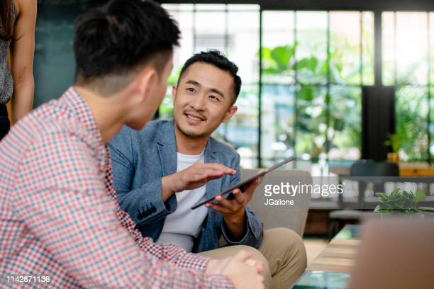 coworkers having an informal meeting in a modern office - jgalione stock pictures, royalty-free photos & images