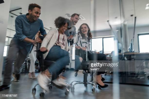 coworkers having fun in the office - só adultos imagens e fotografias de stock