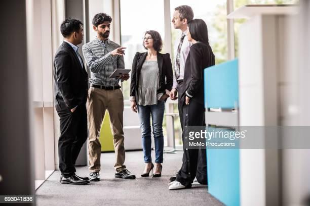 Coworkers having impromptu meeting in modern business office