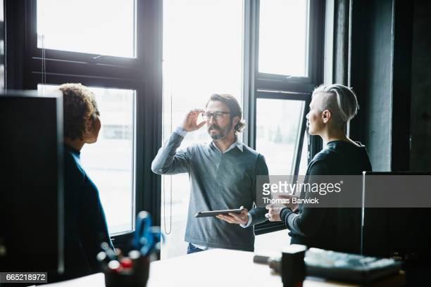Coworkers having informal meeting in high tech office
