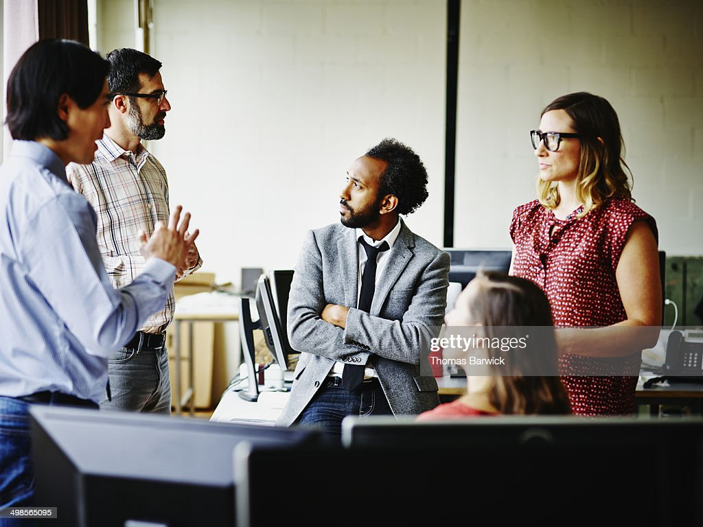 Coworkers having informal meeting in office : Stock Photo