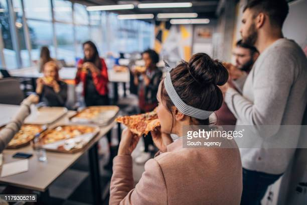 medewerkers met lunchpauze samen in office - lunch stockfoto's en -beelden