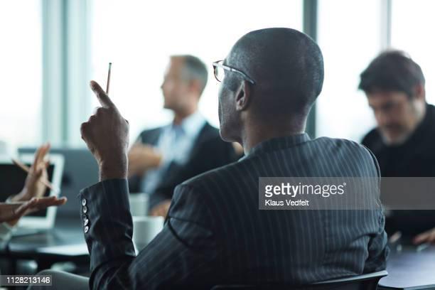co-workers having meeting with laptop in conference room - zwart pak stockfoto's en -beelden