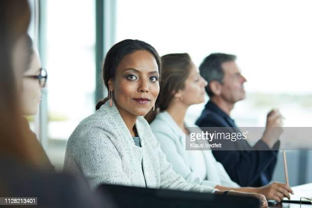 co-workers having meeting with laptop in conference room - grupo pequeño de personas fotografías e imágenes de stock