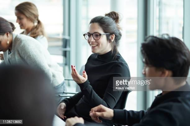 co-workers having meeting with laptop in conference room - brown hair stock pictures, royalty-free photos & images