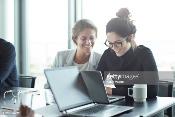 co-workers having meeting with laptop in conference room - collega stockfoto's en -beelden