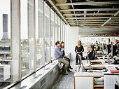 Coworkers having team meeting in office