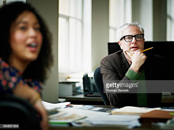 Coworkers having team project discussion in office