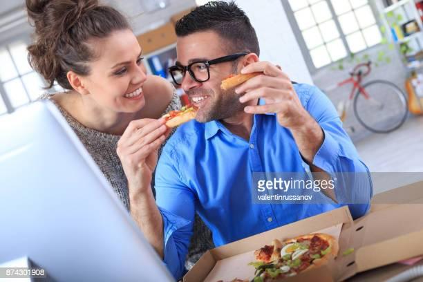 Collaborateurs ayant plaisir et manger des pizzas au travail