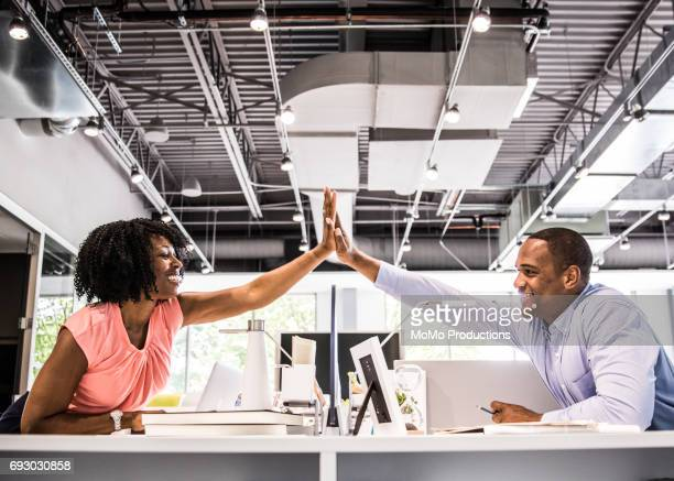 coworkers hi-fiving in modern business office - membro humano - fotografias e filmes do acervo