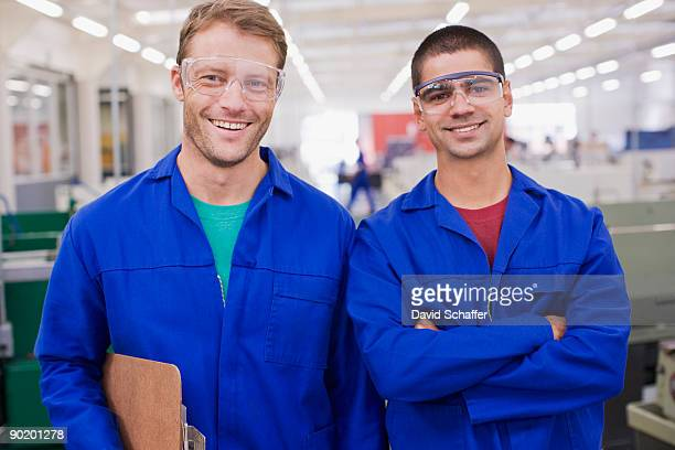 Co-workers in coveralls and safety goggles smiling