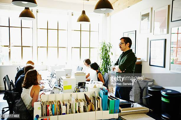 Coworkers in discussion across workstations