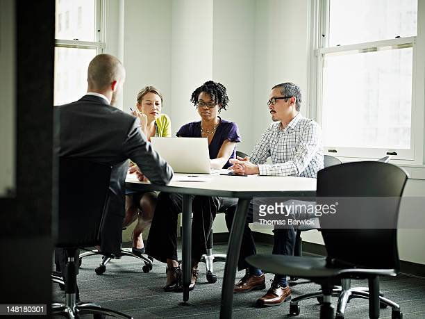 coworkers in discussion at conference room table - leanintogether stock pictures, royalty-free photos & images