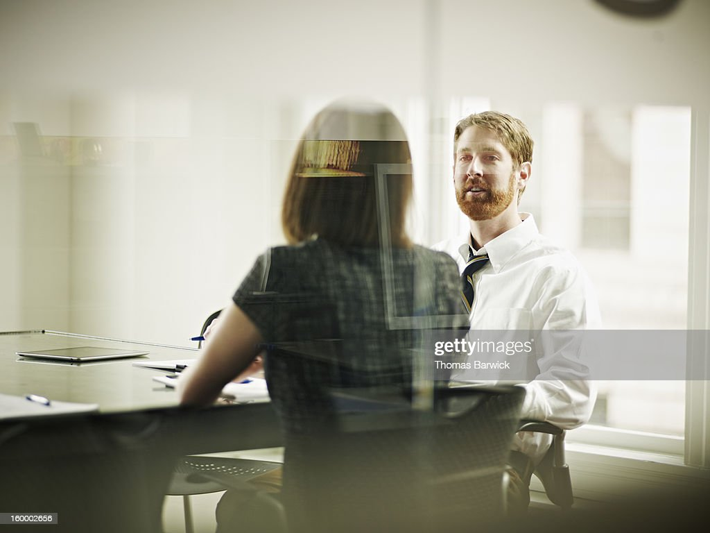 Coworkers in discussion at conference room table : Stock Photo