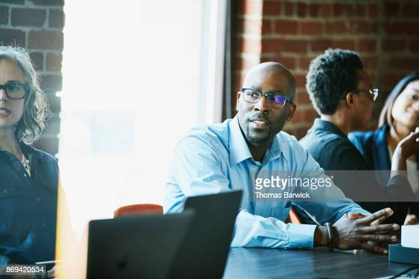 Coworkers in discussion during team meeting in office conference room