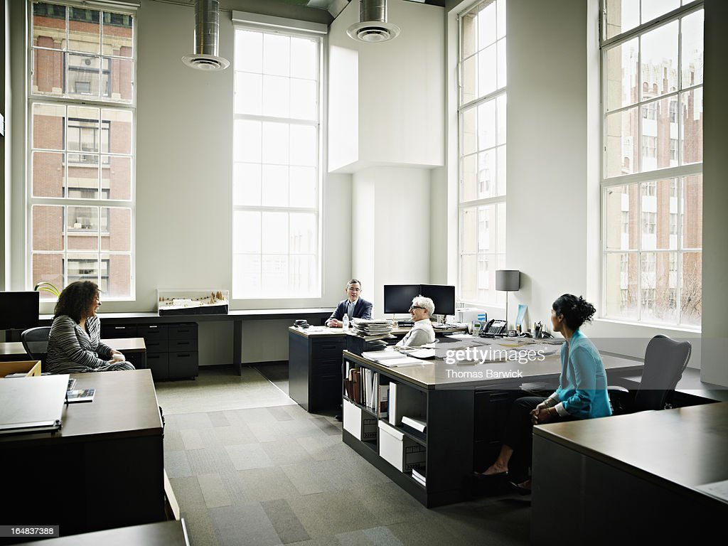 Coworkers in discussion in architects office : Stock Photo