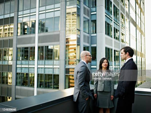 Coworkers in discussion in front of buildings