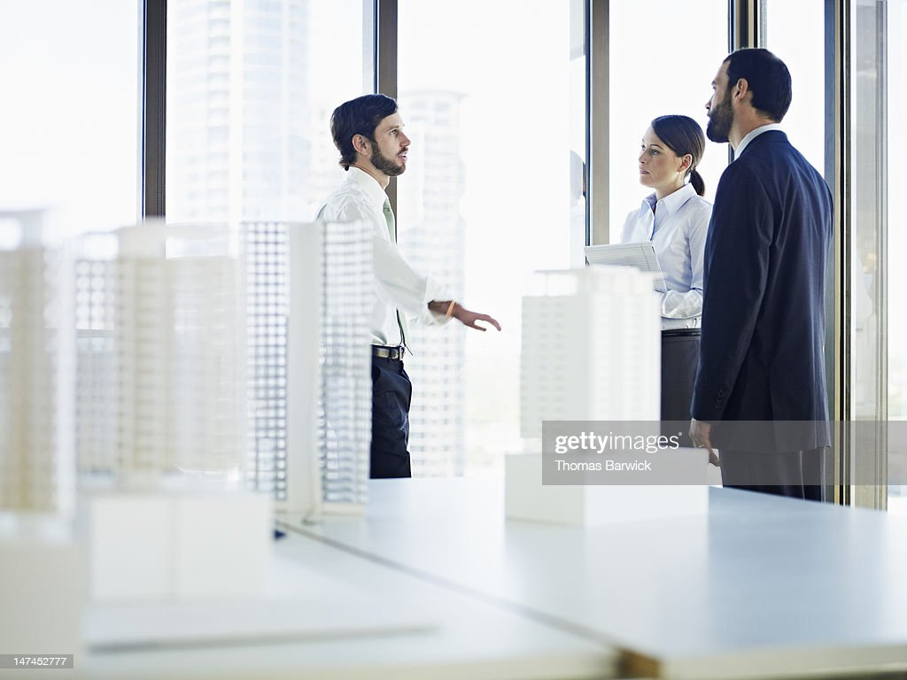 Coworkers in discussion in office near windows : Stock Photo
