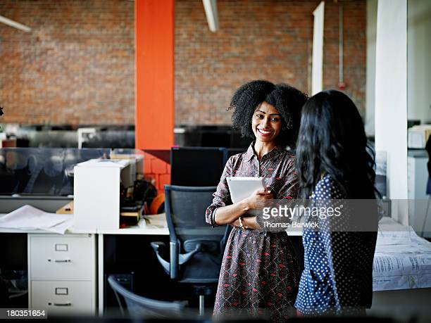 coworkers in discussion in office - leanincollection stock pictures, royalty-free photos & images