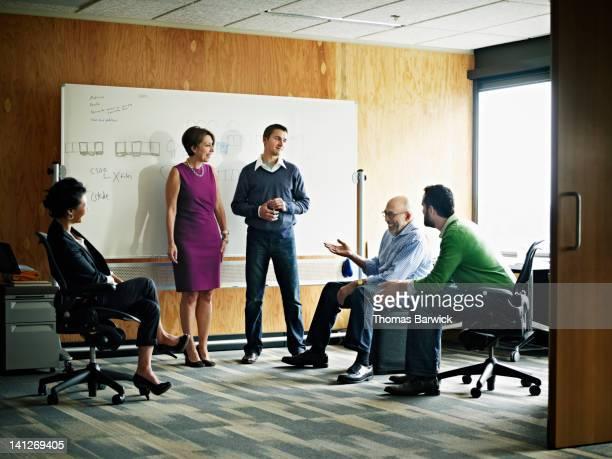 coworkers in discussion in office workstation - cinco pessoas - fotografias e filmes do acervo