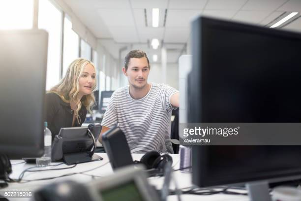 Coworkers in discussion working at workstation