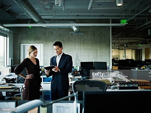 Coworkers in office looking at digital tablet