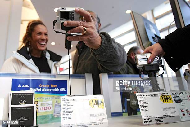 Coworkers Kemberly Richardson left and Albert Webber shop for a digital camera that Richardson is buying for herself at a Best Buy in New York on...