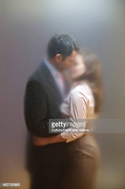 Co-workers kissing behind frosted screen