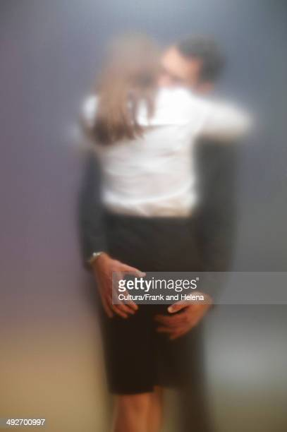 co-workers kissing behind frosted screen - women groping men stock pictures, royalty-free photos & images