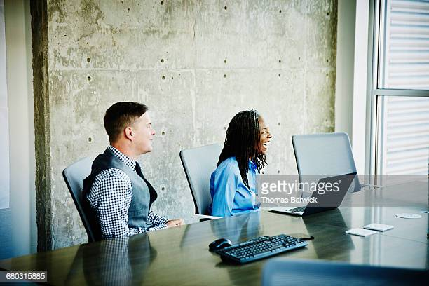 Coworkers laughing during project meeting