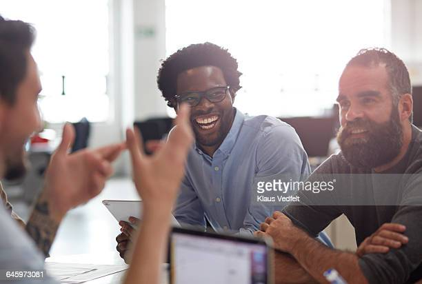 Co-workers laughing together at meeting