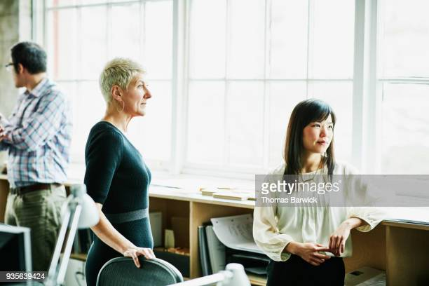 coworkers listening during informal project meeting in design office - older women in short skirts stock pictures, royalty-free photos & images