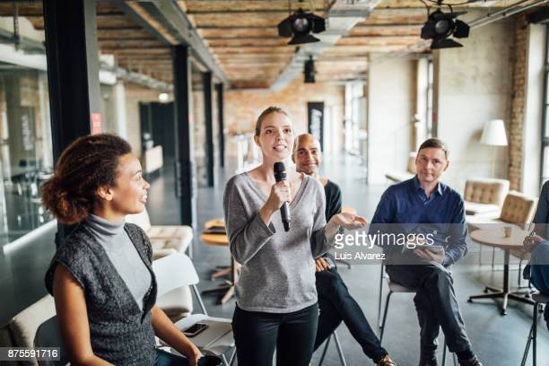 Coworkers listening to businesswoman talking on microphone