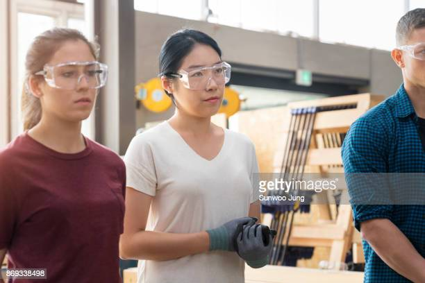 co-workers listening to instructions in workshop. - vanguardians stock pictures, royalty-free photos & images