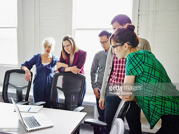 coworkers listening to video conference on laptop - leanintogether stock pictures, royalty-free photos & images