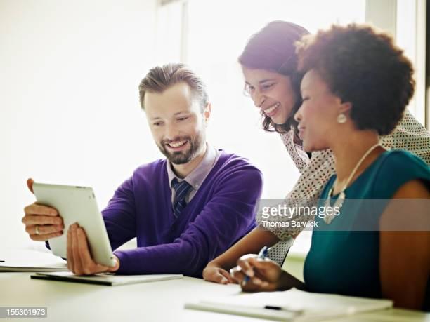 Coworkers looking at digital tablet smiling