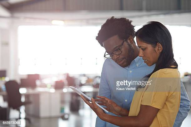 Co-workers looking at tablet together