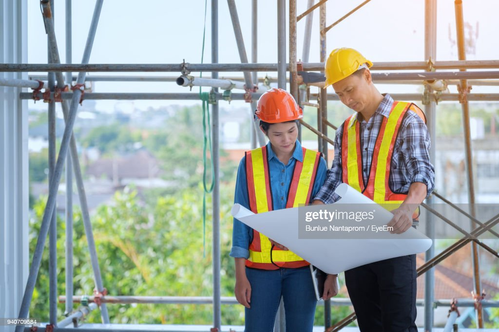 Coworkers looking in blueprint while working at construction site coworkers looking in blueprint while working at construction site stock photo malvernweather