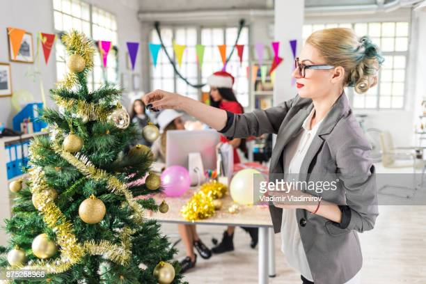 Coworkers making Christmas decoration at workplace