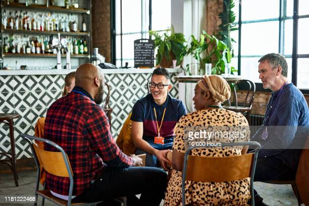 coworkers meeting and relaxing in conference centre bar - organised group stock pictures, royalty-free photos & images