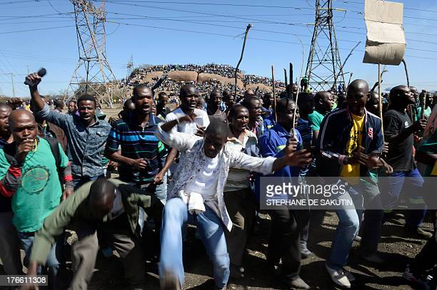 Coworkers of 34 miners shot dead by South African police during a violent wage strike sing and dance on August 16 2013 in Marikana to mark the first...
