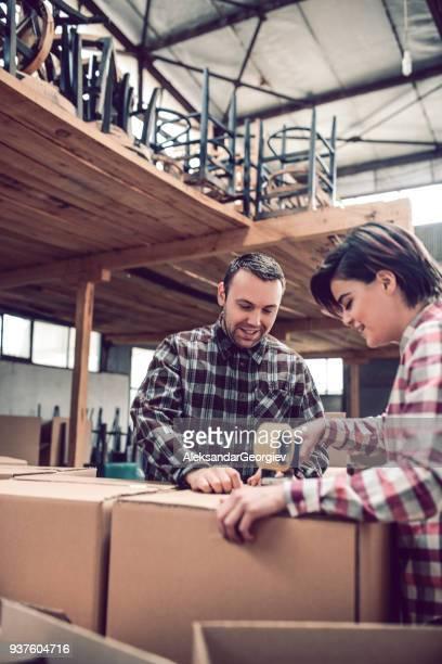 colegas de trabalho embalagem seus produtos para o transporte em sua oficina - postando - fotografias e filmes do acervo