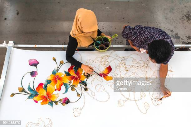 coworkers painting in a batik workshop - tradition stock pictures, royalty-free photos & images