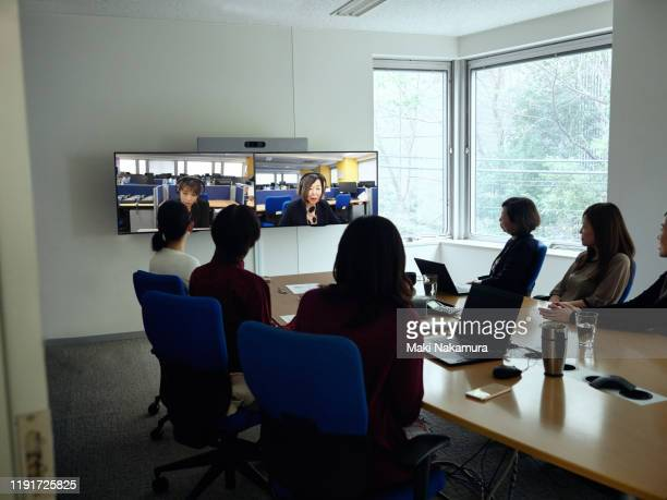coworkers participating in video conference call. - テレビ会議 ストックフォトと画像
