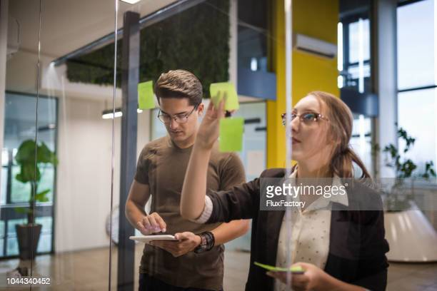 Coworkers planning in the office with a help of adhesive notes