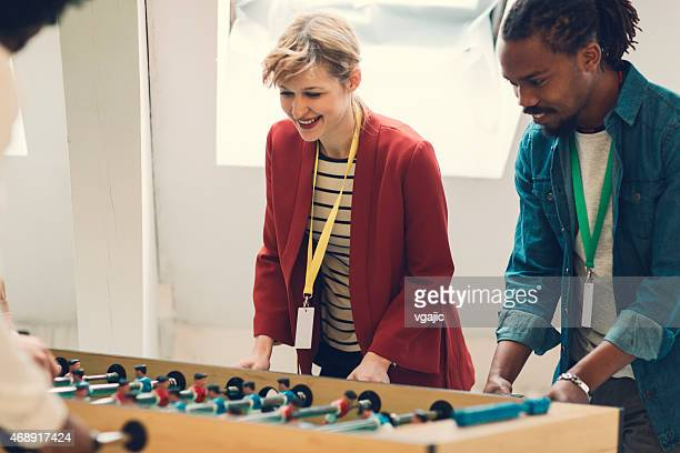 Coworkers Playing Foosball in Creative Startup Business Office.