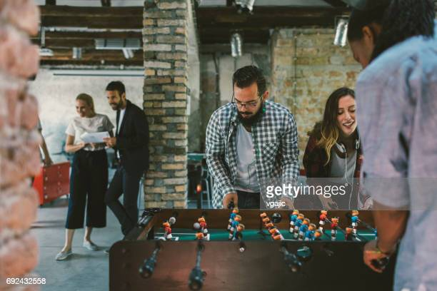 Coworkers playing foosball