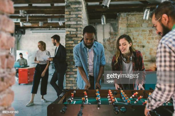 coworkers playing foosball - leisure games stock pictures, royalty-free photos & images