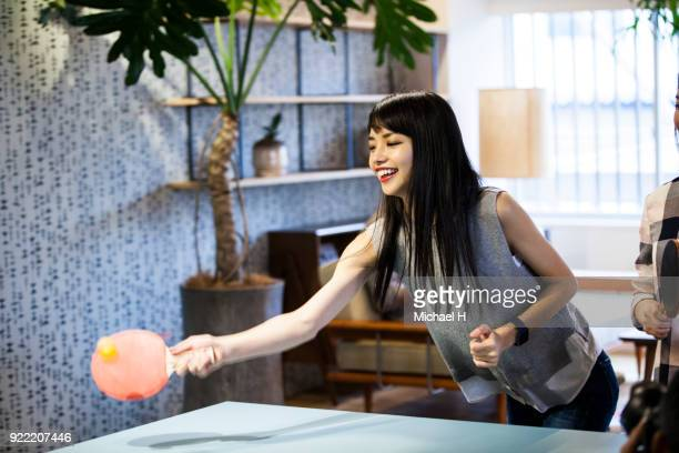 co-workers playing table tennis at the office - table tennis stock pictures, royalty-free photos & images