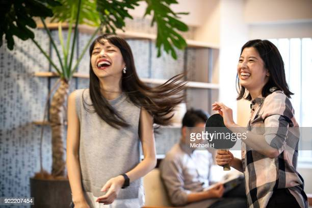 co-workers playing table tennis at the office - east asia stock pictures, royalty-free photos & images